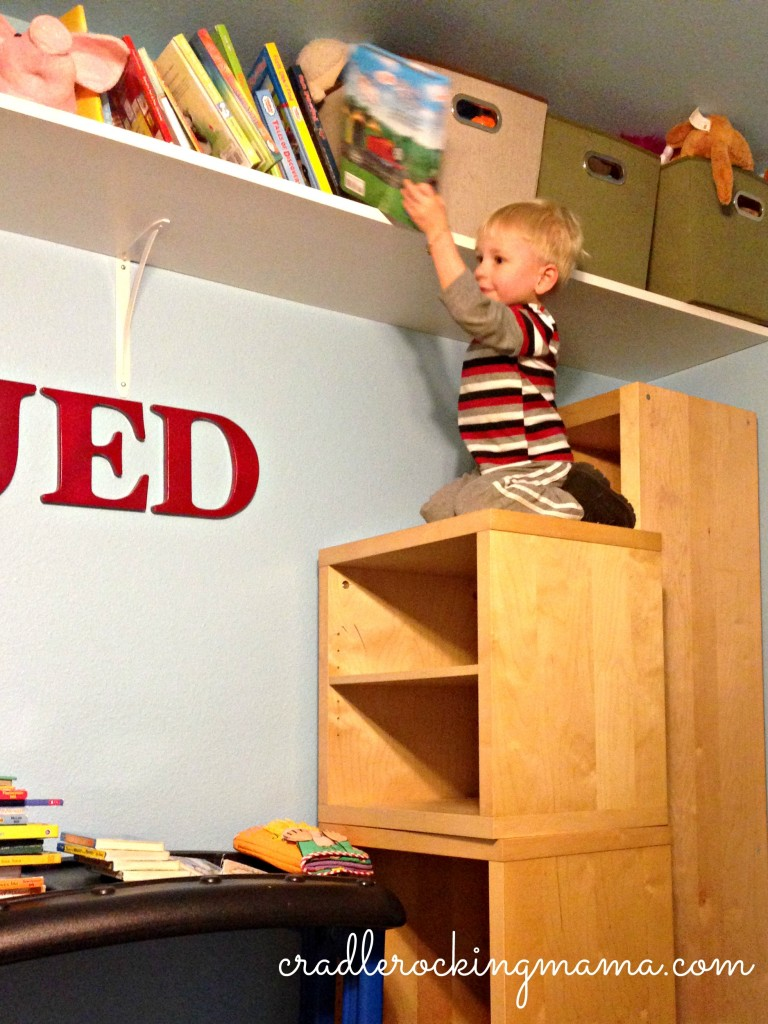 Jed taking advantage of the living room furniture we had to stack in his room to climb and get the books on the HIGH shelf! Little monkey!!