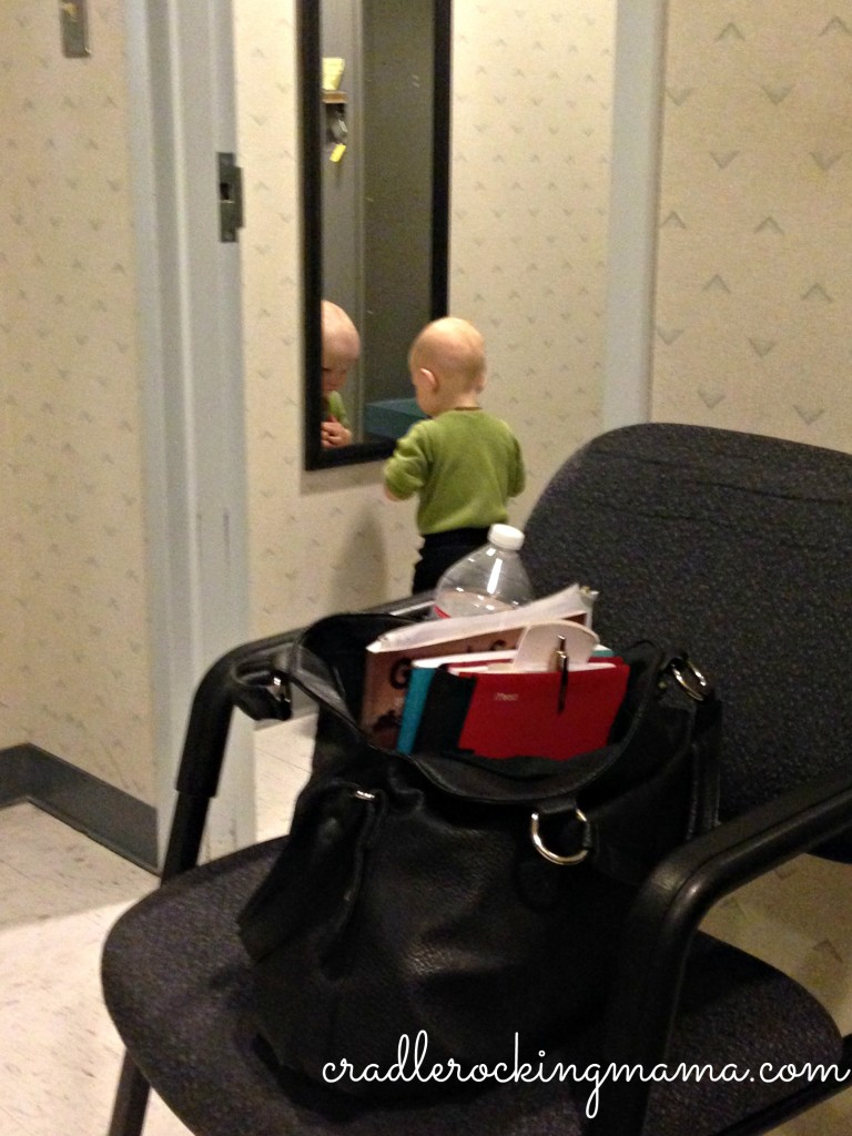 "Zac grinning at the baby in the mirror. Note the gigantic ""mom purse"" in the chair. Ugh."
